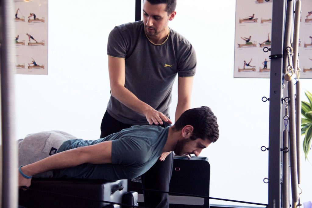 Teacher correcting client in a Pilates class in Greenwich